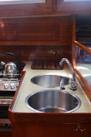Double sinks, top loading fridge in the corner